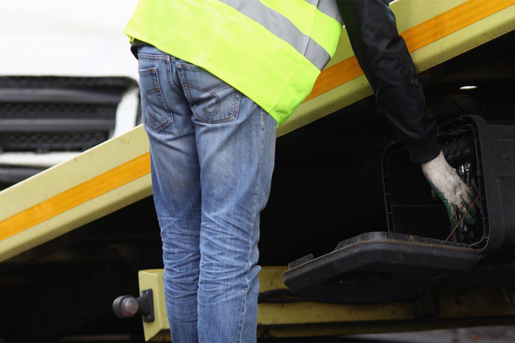 Pracownik pomocy drogowej - prawidłowy załadunek samochodu pozwoli uniknąć dalszych zniszczeń